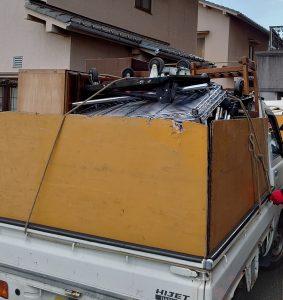 家具等の大型ゴミを軽トラックへ積んでおります。
